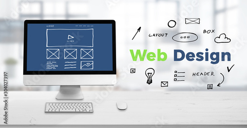 Obraz Web design studio concept with computer display on work desk and web design text surrounded with sketch web page elements. - fototapety do salonu
