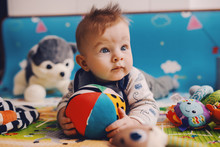 Adorable Curious Caucasian Baby Boy With Big Beautiful Blue Eyes Lying On The Floor On Stomach, Holding Stuffed Ball And Looking Away.