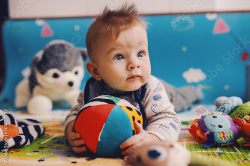 Obraz Adorable curious caucasian baby boy with big beautiful blue eyes lying on the floor on stomach, holding stuffed ball and looking away. - fototapety do salonu
