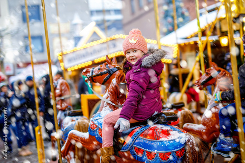Fotografie, Obraz Adorable little kid girl riding on a merry go round carousel horse at Christmas funfair or market, outdoors
