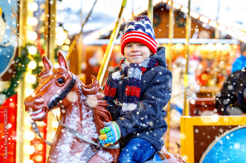 Fotografie, Obraz  Adorable little kid boy riding on a merry go round carousel horse at Christmas funfair or market, outdoors