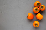 Raw Ripe Orange Persimmons on gray surface, top view. Flat lay, overhead, from above. Space for text.