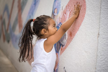 Little Girl Putting Her Hand On A Wall Painting