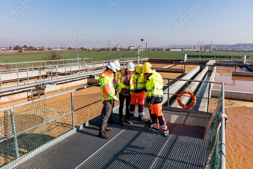 Fényképezés  Engineers and workers assesing wastewater plant