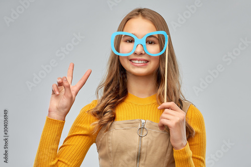 party props, photo booth and people concept - smiling red haired teenage girl with big glasses over grey background