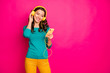 Leinwanddruck Bild - Photo of cheerful nice pretty cute charming girlfriend listening to music in her headphones holding telephone with hands isolated pink vibrant color background