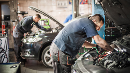 Car mechanic repairer service technician checks and repairs auto engine