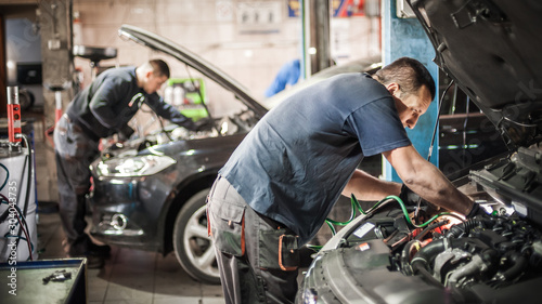 Cuadros en Lienzo  Car mechanic repairer service technician checks and repairs auto engine