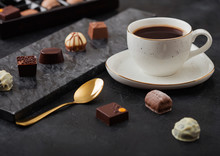 Luxury Chocolate Candies Selection With Cup Of Black Coffee And Golden Spoon On Black Marble Board And Dark Table Background.