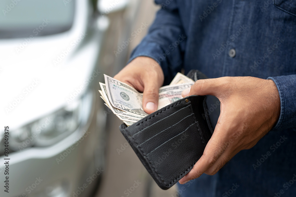 Fototapeta Businessman Person holding a wallet in the hands of take money out of pocket stand front car prepare pay by installments - insurance, loan and buying car finance concept insurance, payment a car