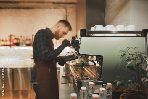 Bearded man barista steaming milk on a professional coffee machine Canvas Print