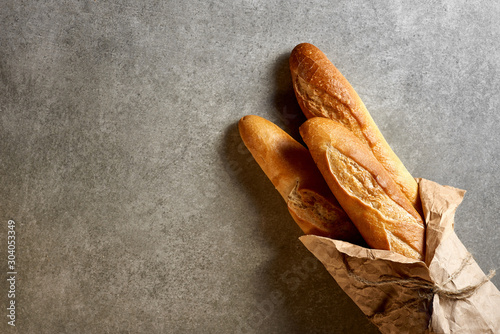 Fototapeta Fresh french baguettes packed in paper on a gray stone surface. Top view. obraz