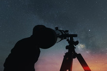 Amateur Astronomy Man With A Telescope Observing The Milky Way Nebulosa At Night. Sunset Light And Empty Copy Space For Editor's Text.