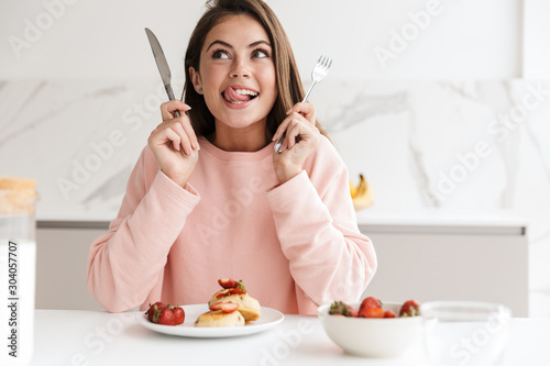 Foto Beautiful smiling young girl having tasty healthy breakfast