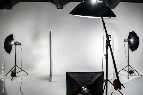 Obraz The interior of the photo studio. Preparing to work with photographic equipment. Cyclorama, background, exposure to light on the octobox, softbox. - fototapety do salonu