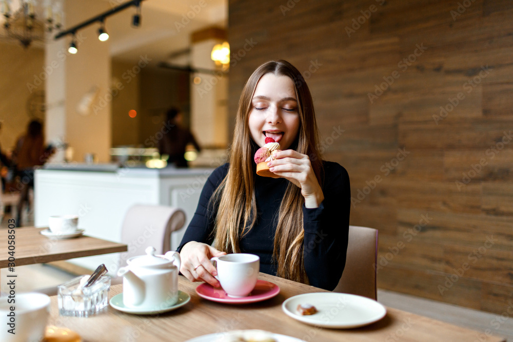 Fototapeta Young woman sits with cafe and enjoys a delicious dessert