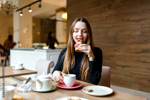 Obraz Young woman sits with cafe and enjoys a delicious dessert - fototapety do salonu