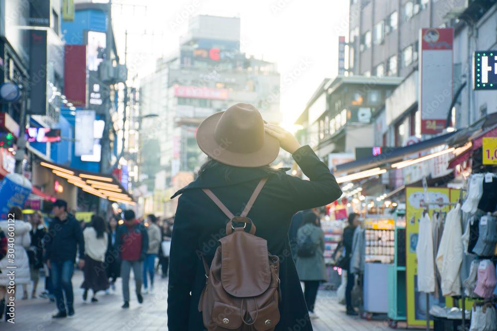 Fototapety, obrazy: Woman tourist is traveling into Hongdae fashion street market in Seoul, Korea.