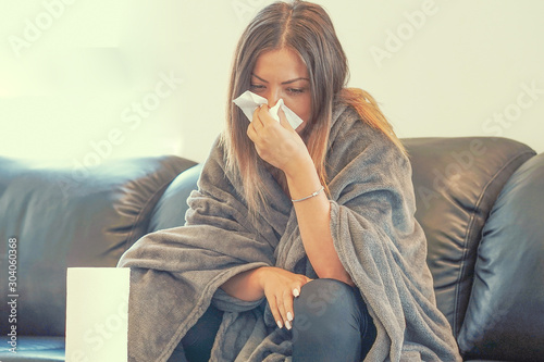Woman feeling cold, freezing, with napkin in a hand, wrapped in blanket, sitting on the sofa Tablou Canvas