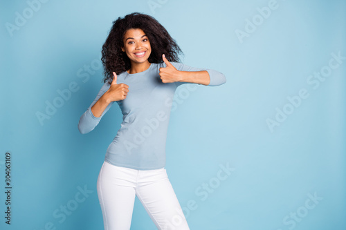 Photo of trendy cheerful positive nice pretty girlfriend leaving positive feedback about goods she purchased smiling toothily showing thumbs up isolated pastel blue color background