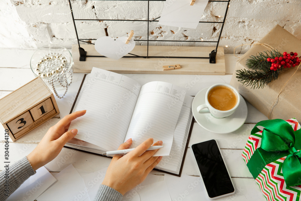 Fototapeta Writes wishes. Dreams of goals plans make a list for writing in notebook. Female hands on a background with wooden calendar, giftbox for New Year, winter holidays and Christmas time. Preparing