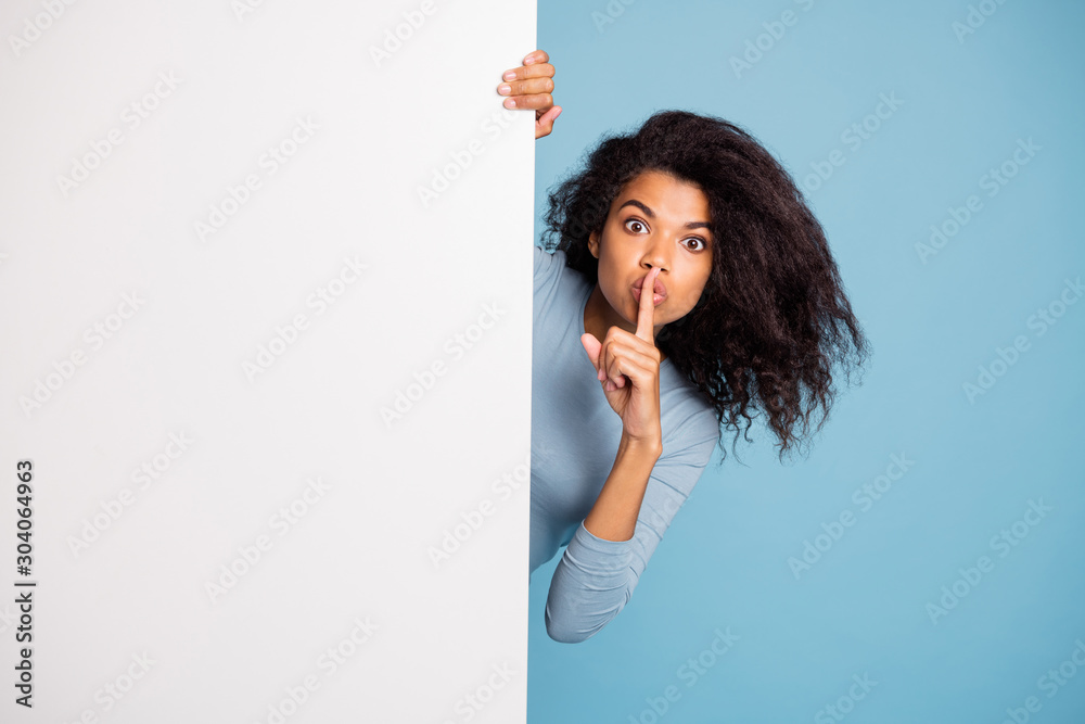 Fototapeta Photo of casual curly wavy beautiful brown haired girl showing you shh sign with forefinger touching her lips looking out of white banner isolated blue pastel color background