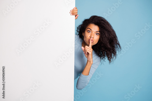 Obraz Photo of casual curly wavy beautiful brown haired girl showing you shh sign with forefinger touching her lips looking out of white banner isolated blue pastel color background - fototapety do salonu