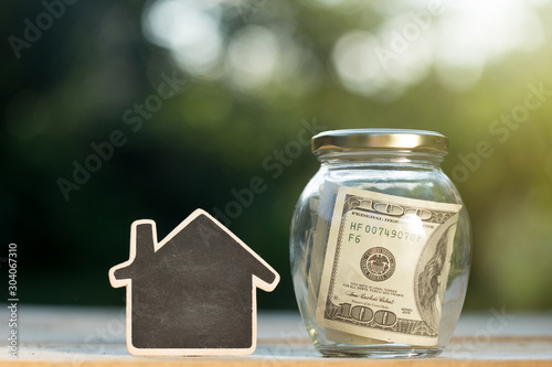 Fototapeta Real estate concept - money jar and little house with space for text on the wooden table in the garden obraz