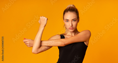 Fitness Lady Stretching Arm Doing Exercise Standing, Yellow Background, Panorama Canvas Print