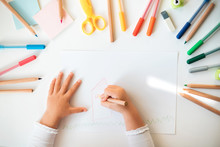 Close Up Of Child's Hands Drawing At White Paper Within Colorful Pens And Pencils.