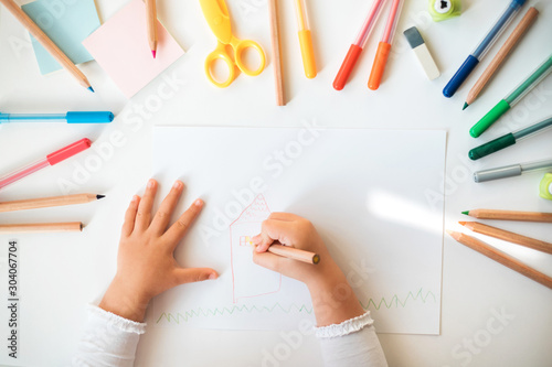 Obraz Close up of child's hands drawing at white paper within colorful pens and pencils. - fototapety do salonu