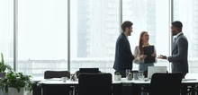 Businesspeople Talking In Office, Standing Against Window