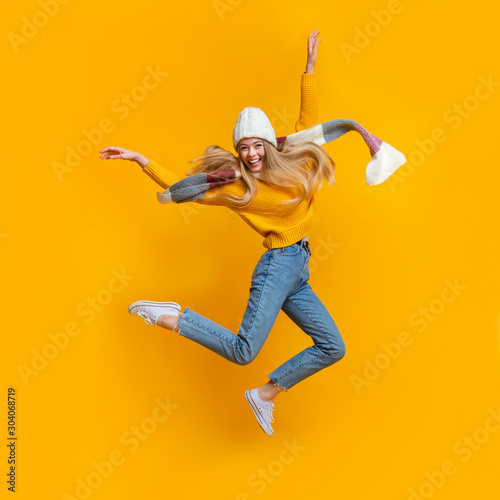 Photo Stands Akt Cheerful winter girl enjoying her life, flying in the air