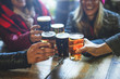 canvas print picture - Group of happy friends drinking and toasting beer at brewery bar restaurant - Friendship concept with young people having fun together at cool vintage pub - Focus on right pint glass - High iso image