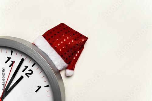 Fényképezés Clock with a Christmas cap on a white background