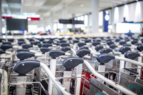 Luggage trolleys at the airport terminal. Fototapet