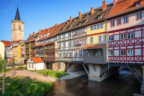 Classic panoramic view of ancient city center of Erfurt with famous Krämerbrücke bridge, colorful houses and historic St Giles' Church on a sunny day with blue sky in summer, Thuringia, Germany