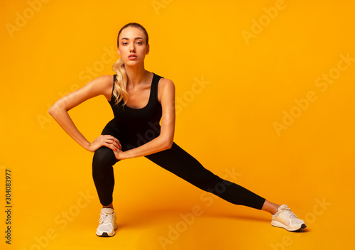 Fototapeta Fitness Woman Doing Side Lunge Stretch Working Out In Studio