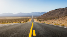Beautiful Panoramic View Of A Long Straight Road Cutting Through A Barren Scenery Of The Wild American Southwest With Extreme Heat Haze On A Hot And Sunny Day With Blue Sky In Summer