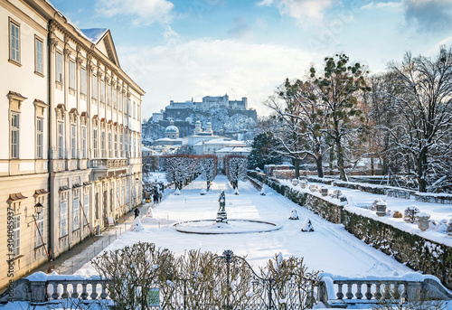 Obraz Classic view of famous Mirabell Gardens in the historic city of Salzburg with Hohensalzburg Fortress in golden evening light on a beautiful sunny day with blue sky in winter, Salzburger Land, Austria - fototapety do salonu