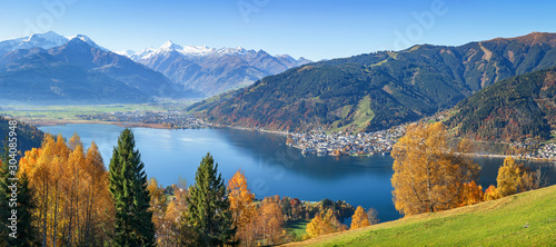 Foto op Plexiglas Herfst Panoramic view of beautiful autumn scene in the Alps with crystal clear Zeller lake, golden leaves and famous Kitzsteinhorn on a sunny day with blue sky in fall, Zell am See, Salzburger Land, Austria