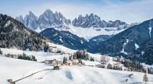 Classic Panoramic View Of Famous Dolomites Mountain Peaks With The Idyllic Village Val Di Funes And Historic Church Of St. Magdalena On A Scenic Sunny Day With Blue Sky In Winter, South Tyrol, Italy