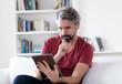 canvas print picture - Mann mit grauen Haaren liest online Nachrichten