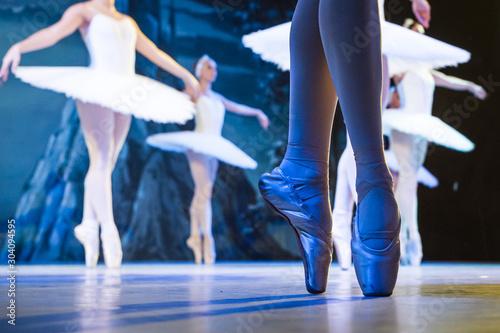 Photo Legs of ballerinas dancing in ballet Swan Lake.