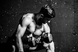 Young strong muscular sweaty fit man biceps muscle cross workout training with heavy dumbbell weight in the gym dark image with shadows real people black and white