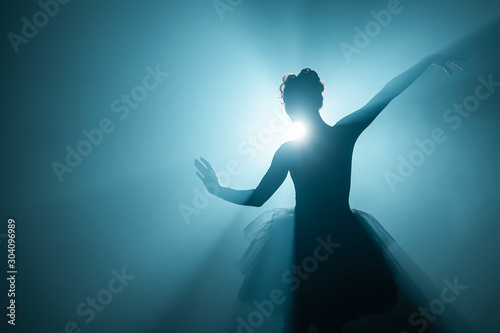 Fotomural Ballerina in black tutu dress dancing on stage with magic blue light and smoke