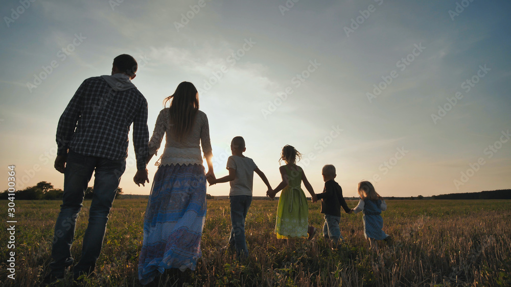 Fototapety, obrazy: A large family of six people walk on the floor at sunset.
