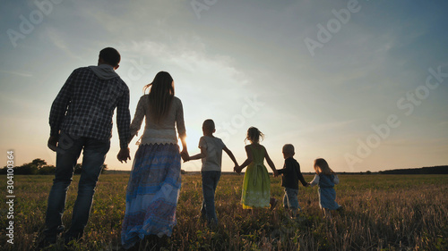 Photographie  A large family of six people walk on the floor at sunset.