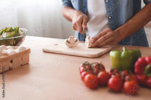 Obraz close up of man hands slicing mushrooms for salad - fototapety do salonu