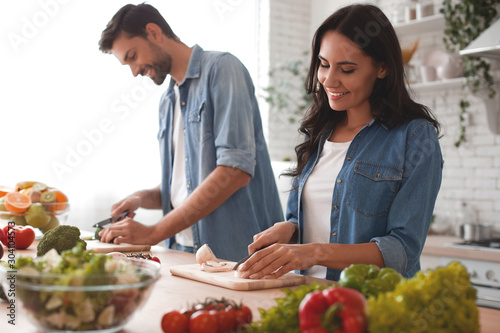 Fototapeta smiling wife and husband cooking dinner in the kitchen together obraz